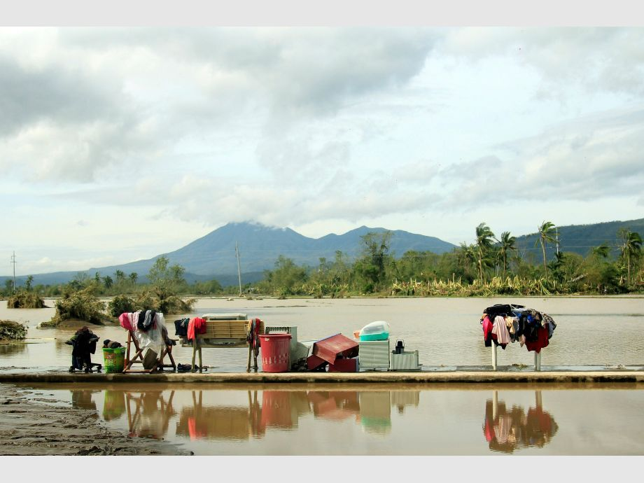Residents dry their clothes along a flooded highway in Malinao, Albay - NARCH/NARCH30 - Filipinas Tifón