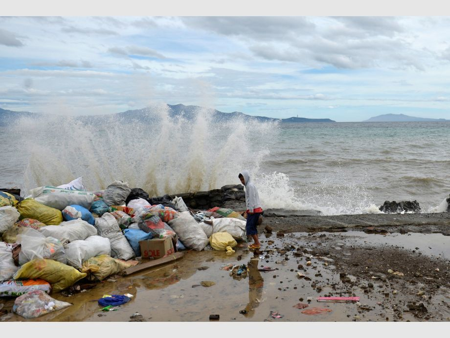 A boy stands at a partially damaged port, as strong waves hit the shore after Typhoon Nock-Ten hit Mabini, Batangas - Filipinas Tifón