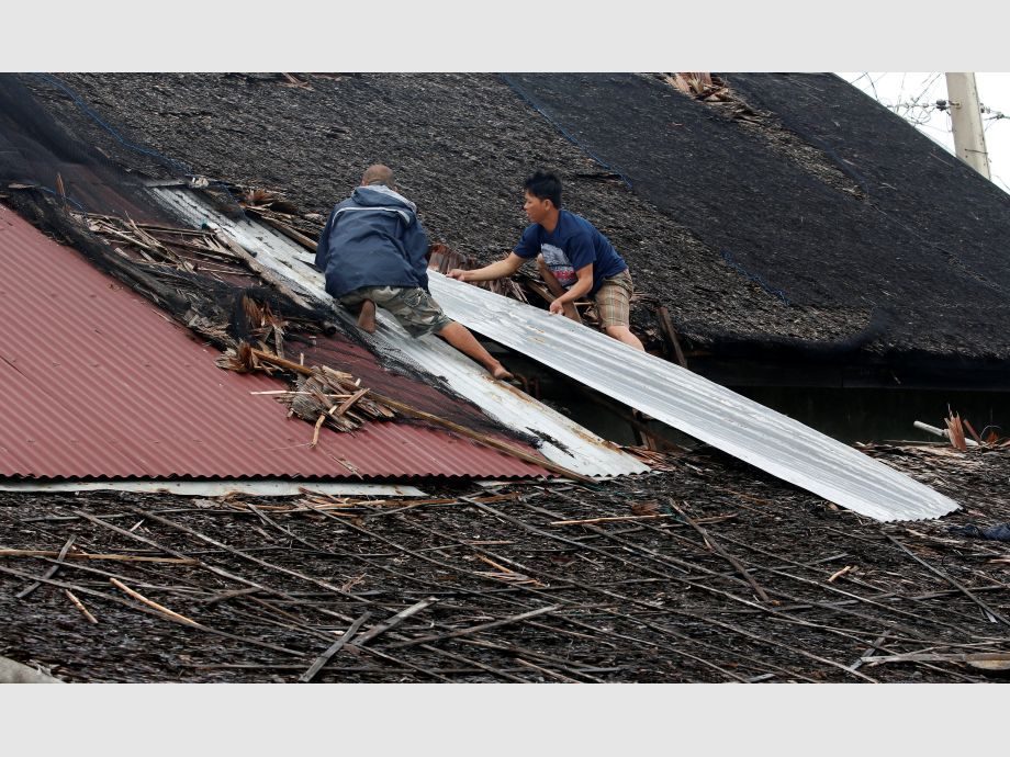 Residents fix their partially damaged roof after Typhoon Nock Ten hit Mabini, Batangas - Filipinas Tifón