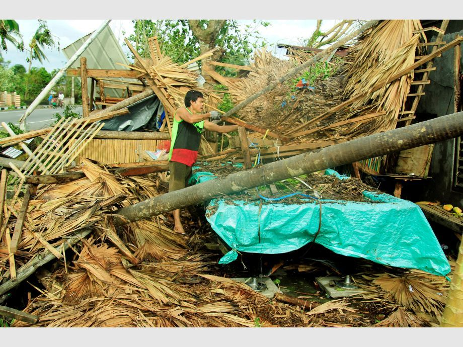 A resident retrieves belongings from his destroyed house after Typhoon Nock-Ten hit Malinao, Albay - NARCH/NARCH30 - Filipinas Tifón