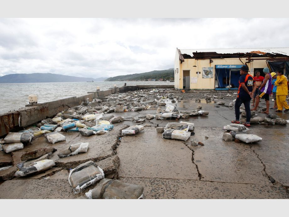 Residents gather in a partially damaged port in Mabini, Batangas, after it was hit by Typhoon Nock-Ten - Filipinas Tifón