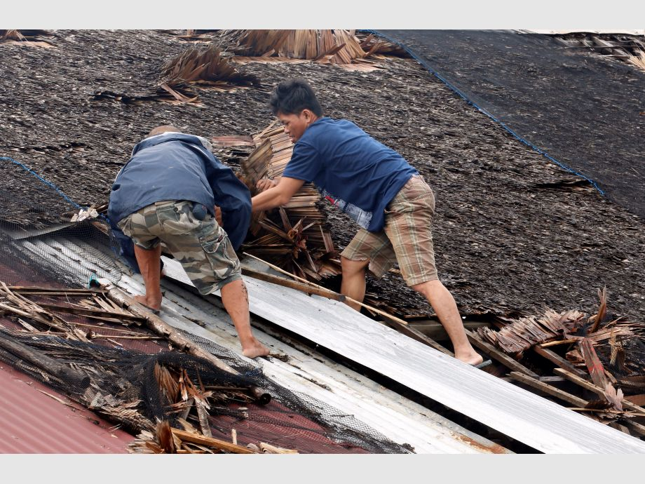 Residents fix their partially damaged roof after Typhoon Nock-Ten hit Mabini, Batangas - Filipinas Tifón