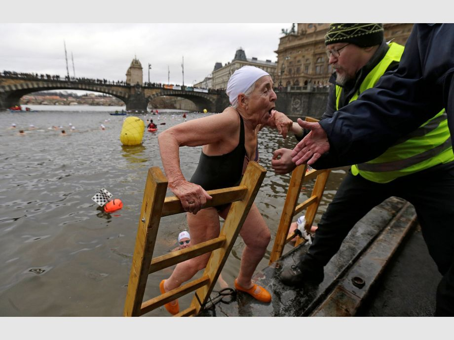 A swimmer is helped out of the Vltava river after the annual Christmas winter swimming competition in Prague - República Checa Natación