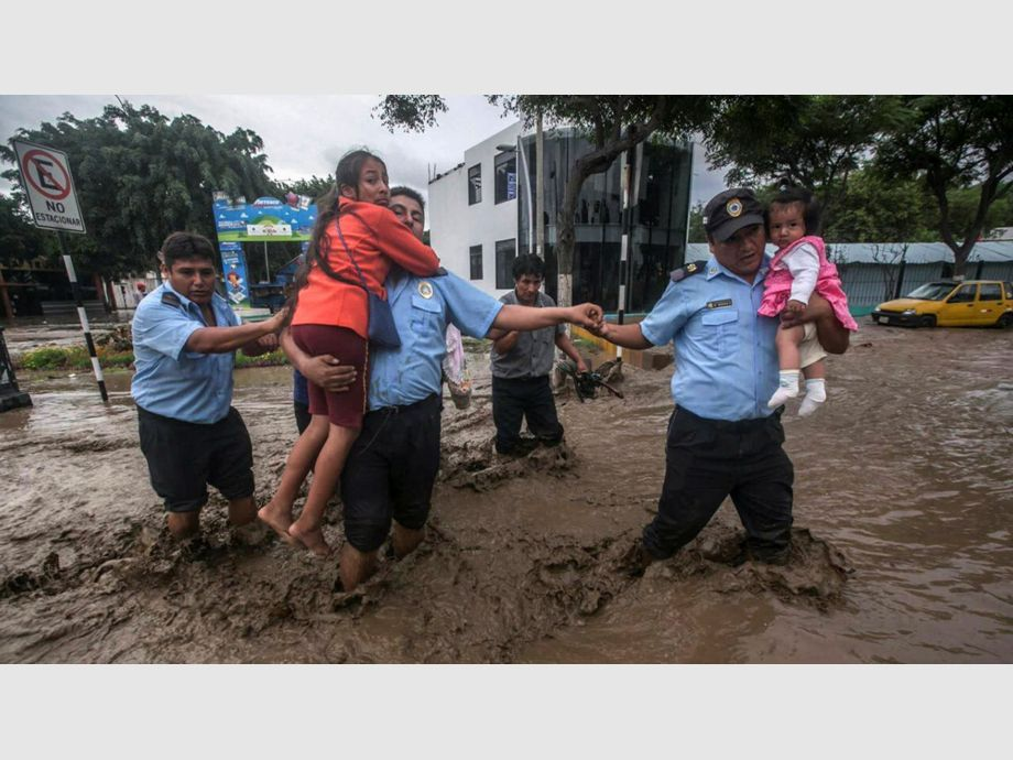 Municipality guards help residents cross a flooded street in Trujillo, northern Peru - Municipality guards help residents cross a flooded street in Trujillo, northern Peru, March 15, 2017. REUTERS/Douglas Juarez FOR EDITORIAL USE ONLY. NO RESALES. NO ARCHIVES - NARCH - Trágicos aludes en Perú