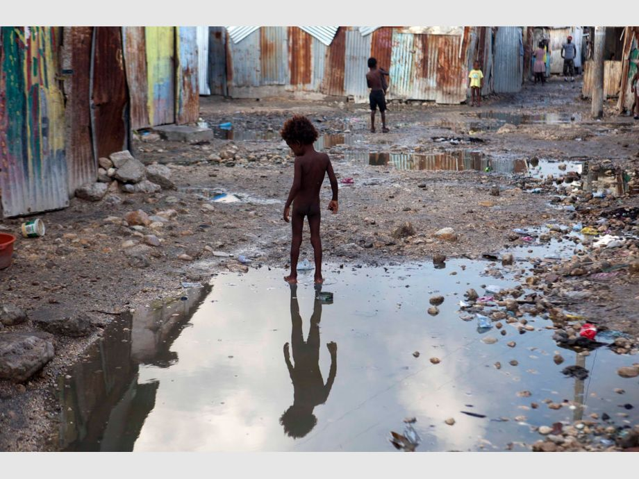 A child plays in a puddle in the seaside slum of Port-au-Prince, Haiti, Wednesday, Sept. 6, 2017. Heavy rain and 185-mph winds lashed the Virgin Islands and Puerto Rico - Huracán Irma