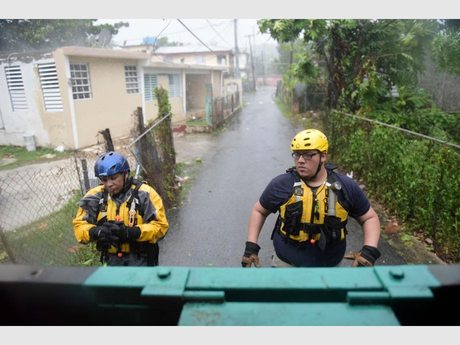 Julio Feliciano (left, and Adrian Colon, right, both rescue staff members from the Municipal Emergency Management Agency toured the streets of the Matelnillo community searching for citizens in distress during the passage of Hurricane Irma through the northeastern part of the island in Fajardo, Puerto Rico, Wednesday, Sept. 6, 2017. The US territory was first to declare a state of emergency las Monday, as the National Hurricane Center forecast that the storm would strike the Island Wednesday. (AP Photo/Carlos Giusti) - PUERTO RICO OUT-NO PUBLICAR EN PUERTO RICO - Huracán Irma