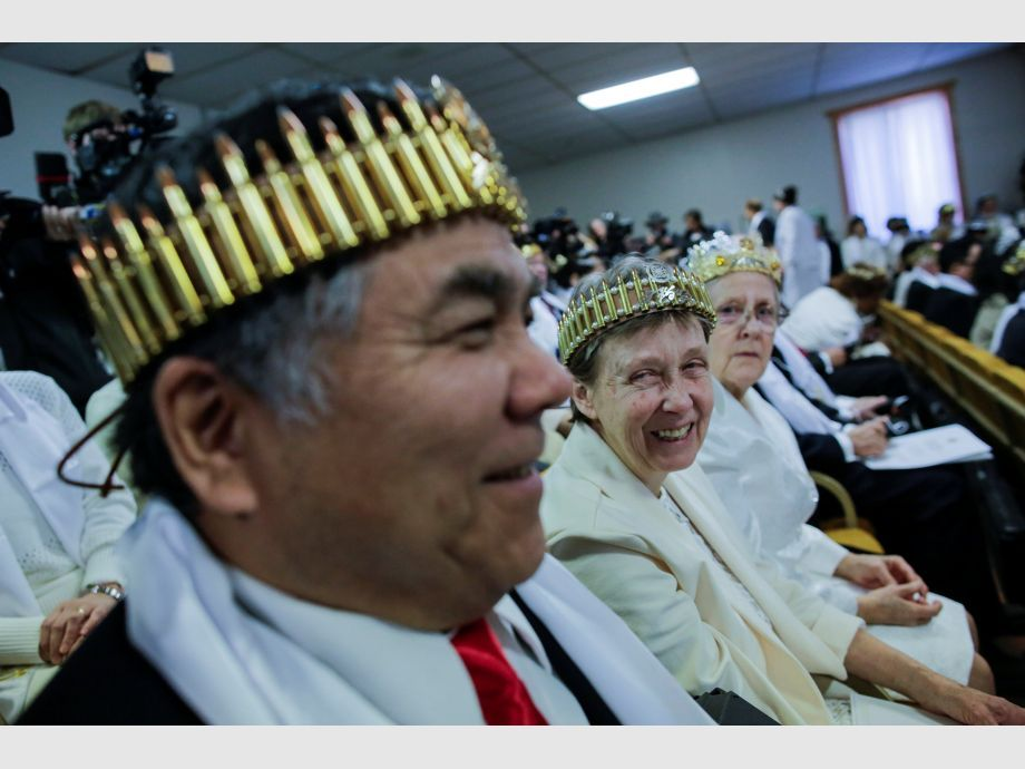A couple wearing bullet crowns sit with their AR-15-style rifles in their cases, as people attend a blessing ceremony at the Sanctuary Church in Newfoundland - Estados Unidos