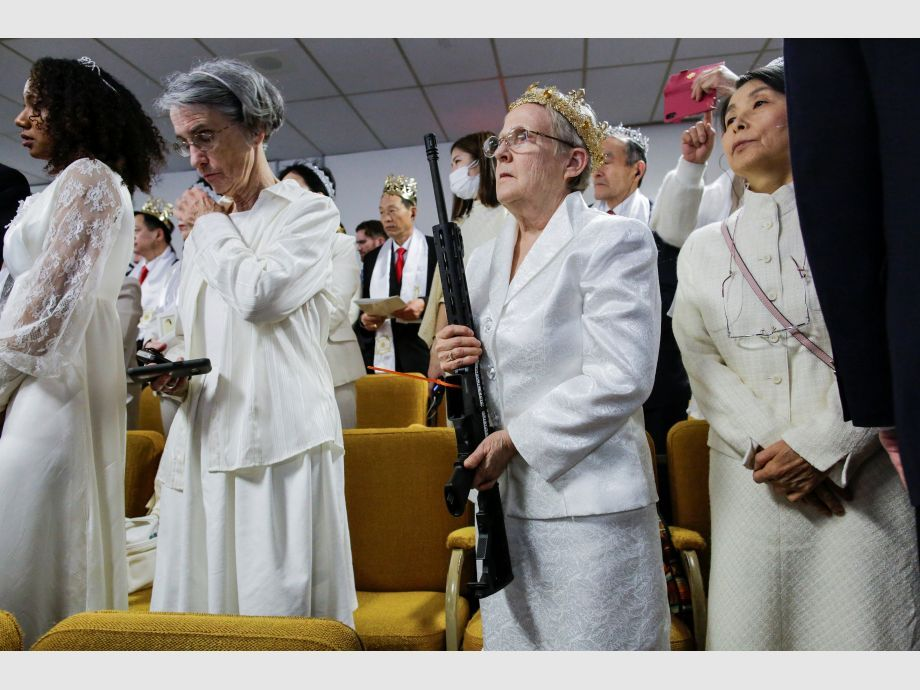 A woman holds her AR-15-style rifle as people attend a blessing ceremony with their AR-15-style rifles in their cases at the Sanctuary Church in Newfoundland - Estados Unidos