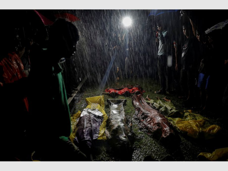 AWARD WINNER: Pulitzer for Feature Photography - People gather under heavy rain around bodies of Rohingya refugees after the boat they were using to flee violence in Myanmar capsized off Inani Beach near Cox -