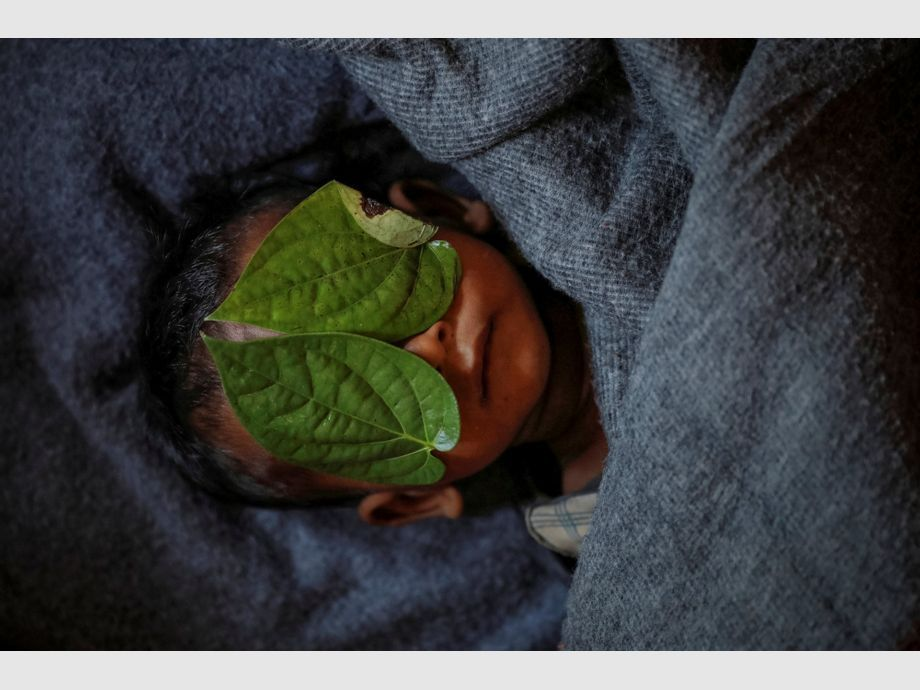 AWARD WINNER: Pulitzer for Feature Photography - Betel leaves cover the face of 11-month-old Rohingya refugee Abdul Aziz whose wrapped body lay in his family shelter after he died battling high fever and sever cough at the Balukhali refugee camp near Cox -