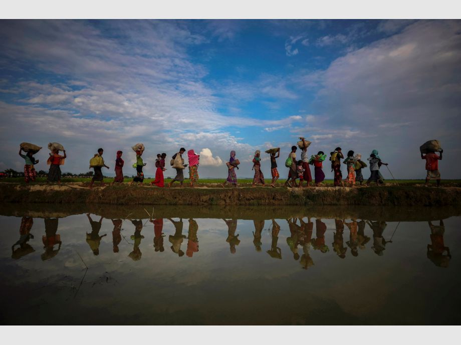 AWARD WINNER: Pulitzer for Feature Photography - Rohingya refugees are reflected in rain water along an embankment next to paddy fields after fleeing from Myanmar into Palang Khali, near Cox -