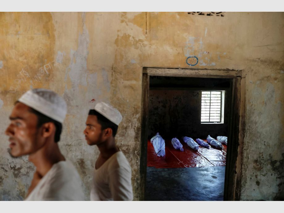 AWARD WINNER: Pulitzer for Feature Photography - Bodies of Rohingya refugees, who died when their boat capsized while fleeing Myanmar, are placed in a local madrasa in Shah Porir Dwip, in Teknaf, near Cox -