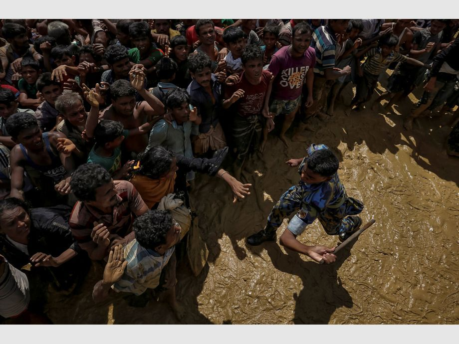 AWARD WINNER: Pulitzer for Feature Photography - A security officer attempts to control Rohingya refugees waiting to receive aid in Cox -