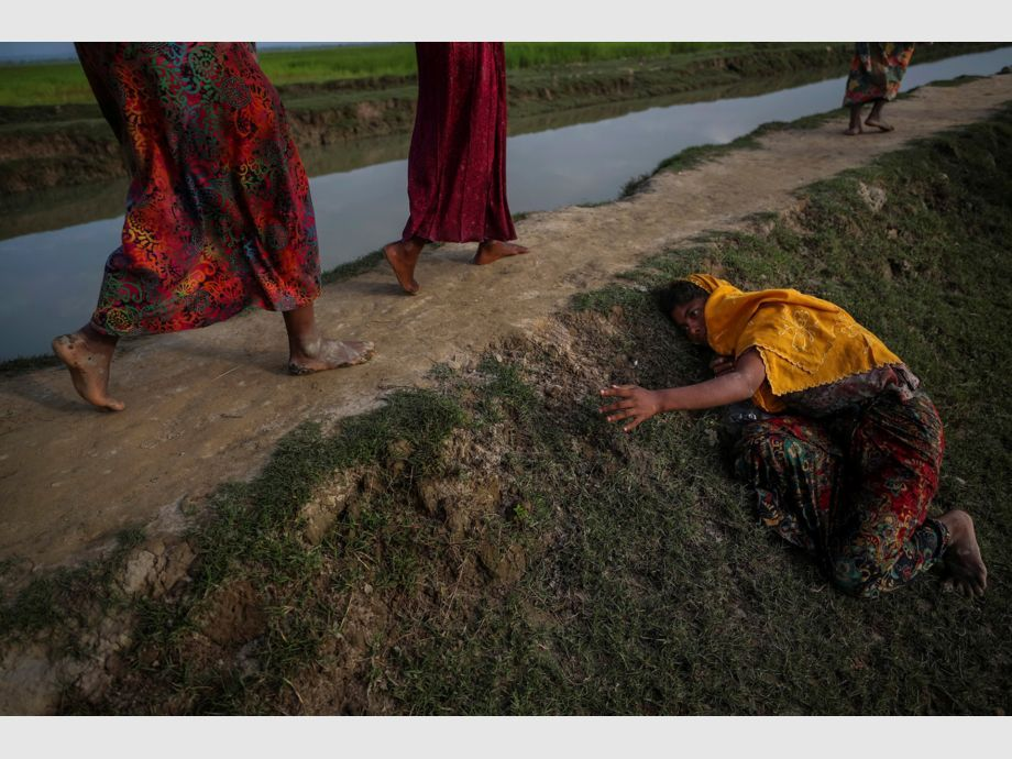 AWARD WINNER: Pulitzer for Feature Photography - An exhausted Rohingya refugee fleeing violence in Myanmar cries for help from others crossing into Palang Khali, near Cox -
