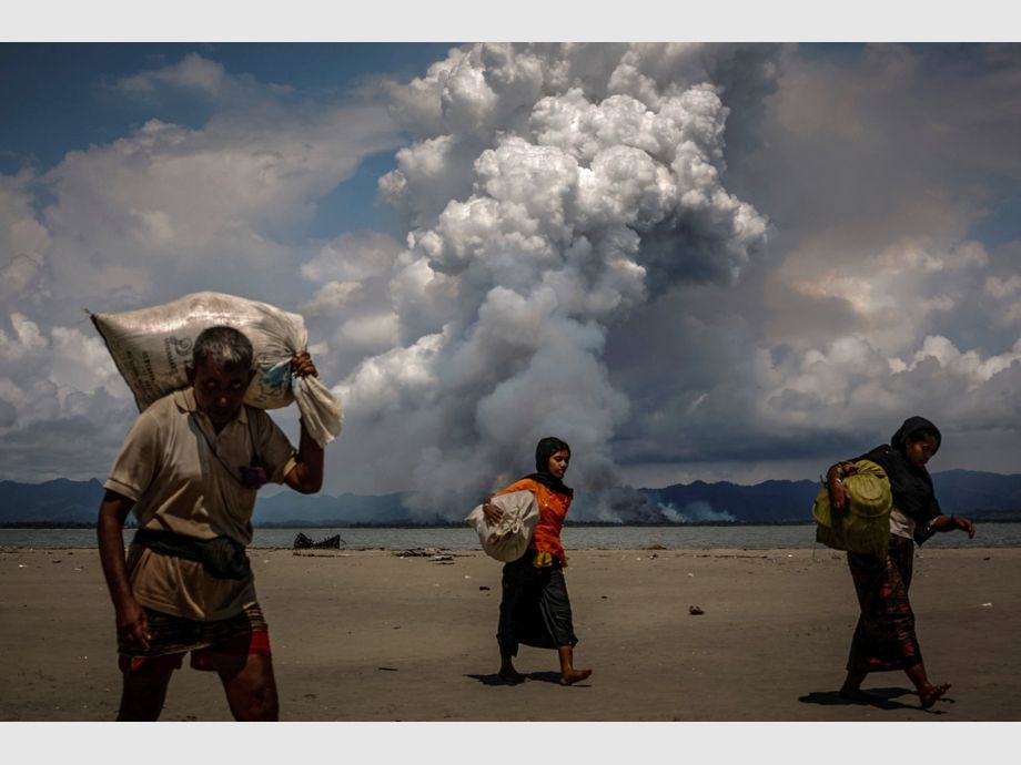 AWARD WINNER: Pulitzer for Feature Photography - Smoke is seen on the Myanmar border as Rohingya refugees walk on the shore after crossing the Bangladesh-Myanmar border by boat through the Bay of Bengal, in Shah Porir Dwip, Bangladesh September 11, 2017. REUTERS/Danish Siddiqui    TO FIND ALL PICTURES SEARCH REUTERS PULITZER -