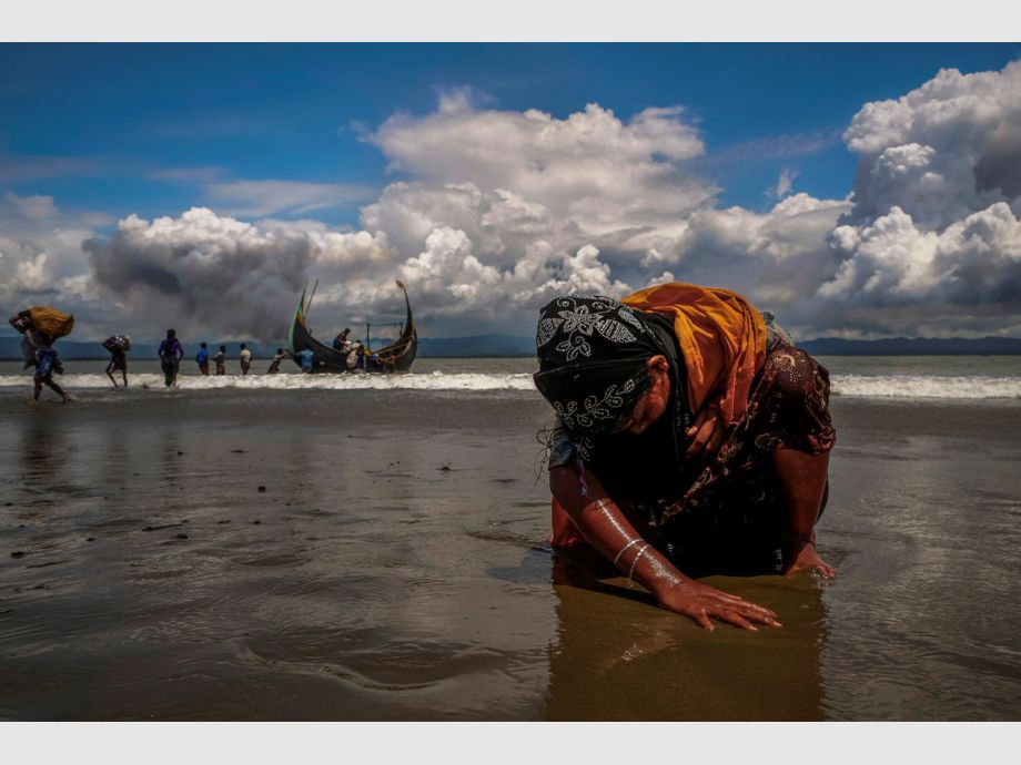 AWARD WINNER: Pulitzer for Feature Photography - An exhausted Rohingya refugee woman touches the shore after crossing the Bangladesh-Myanmar border by boat through the Bay of Bengal, in Shah Porir Dwip, Bangladesh September 11, 2017. REUTERS/Danish Siddiqui    TO FIND ALL PICTURES SEARCH REUTERS PULITZER -