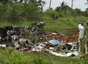 A rescue team member works at the wreckage of a Boeing 737 plane that crashed in the agricultural area of Boyeros, around 20 km south of Havana - Tragedia aérea en Cuba