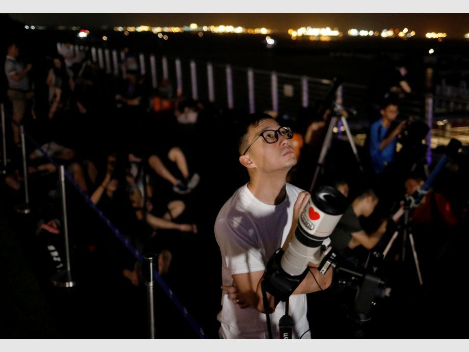 Astronomy enthusiasts wait to see the lunar eclipse of a blood moon at Marina South Pier in Singapore - eclipse de luna