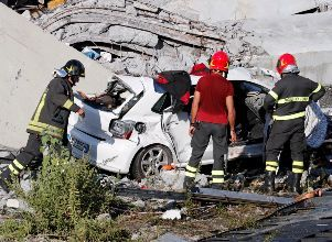Firefighters stand inspect crushed car at collapsed Morandi Bridge site in Genoa - Tragedia en Italia