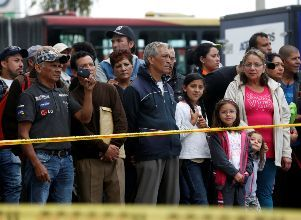 People stand beside a security tape set up close to the scene where a car bomb exploded, according to authorities, in Bogota - Terrorismo Colombia