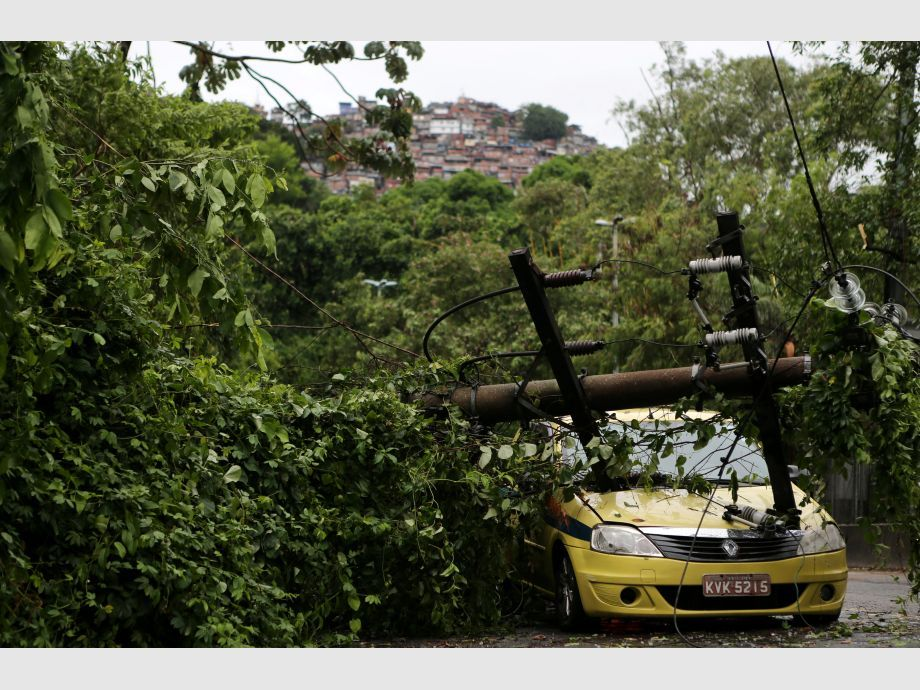 An electric post is seen fallen over a taxi after heavy rains in Gavea neighborhood in Rio de Janeiro - río de janeiro Brasil
