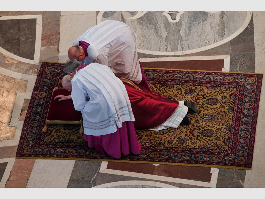 Monsignor Guido Marini helps Pope Francis lie on the floor during the Lord -