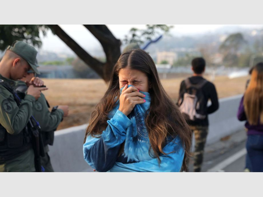 A woman reacts to tear gas near the Generalisimo Francisco de Miranda Airbase in Caracas - A woman reacts to tear gas near the Generalisimo Francisco de Miranda Airbase