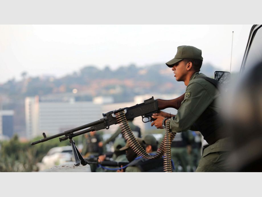 A military member aims a weapon near the Generalisimo Francisco de Miranda Airbase in Caracas - A military member aims a weapon near the Generalisimo Francisco de Miranda Airbase