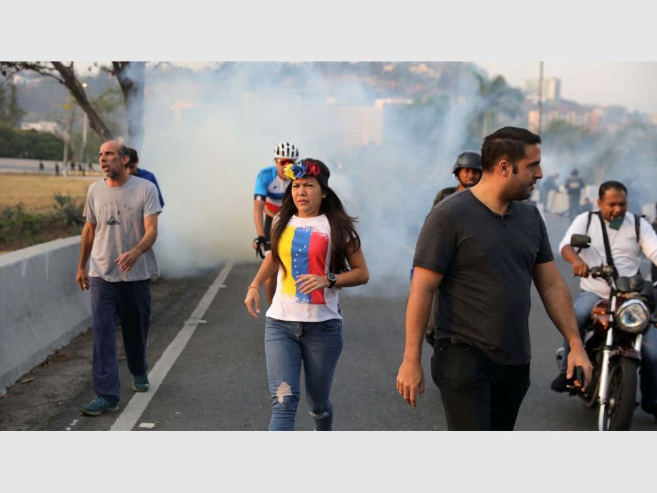People run away from tear gas near the Generalisimo Francisco de Miranda Airbase in Caracas - People run away from tear gas near the Generalisimo Francisco de Miranda Airbase