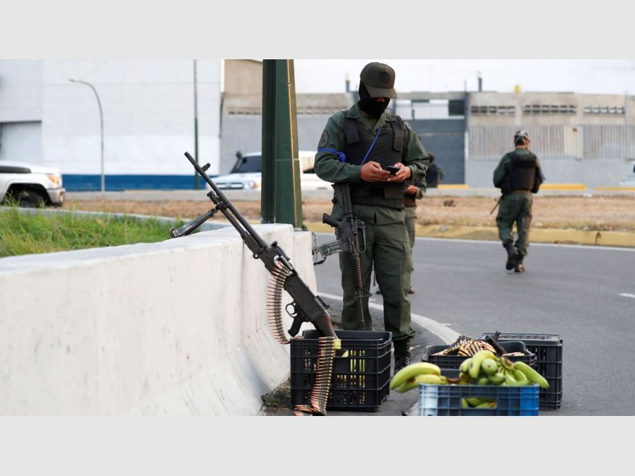 A military member uses his phone near the Generalisimo Francisco de Miranda Airbase in Caracas - A military member uses his phone near the Generalisimo Francisco de Miranda Airbase