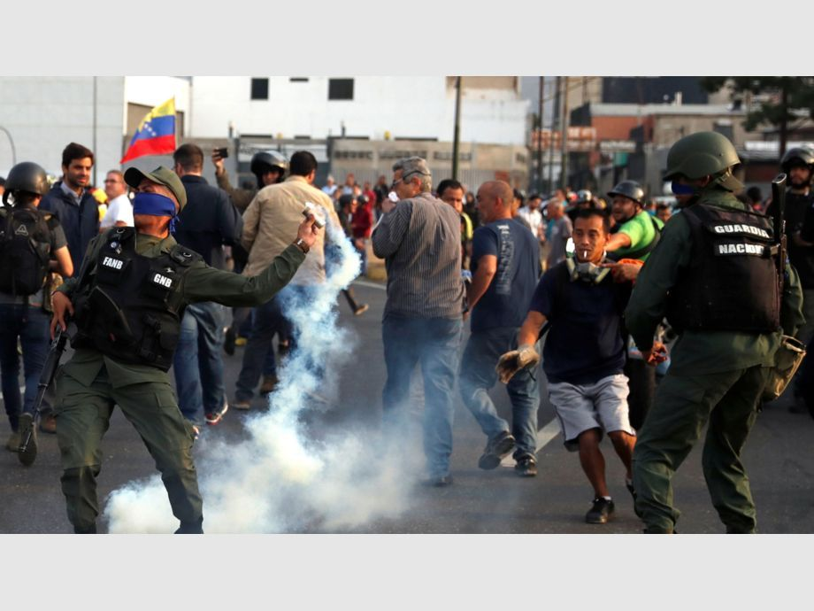 A military member throws a tear gas canister near the Generalisimo Francisco de Miranda Airbase in Caracas - A military member throws a tear gas canister near the Generalisimo Francisco de Miranda Airbase
