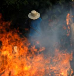 FILE PHOTO: A man works in a burning tract of Amazon jungle as it is being cleared by loggers and farmers in Iranduba - amazonas