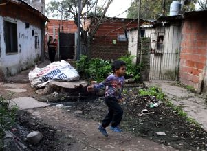 A boy runs in the Matadero shanty town in Quilmes - pobreza uca