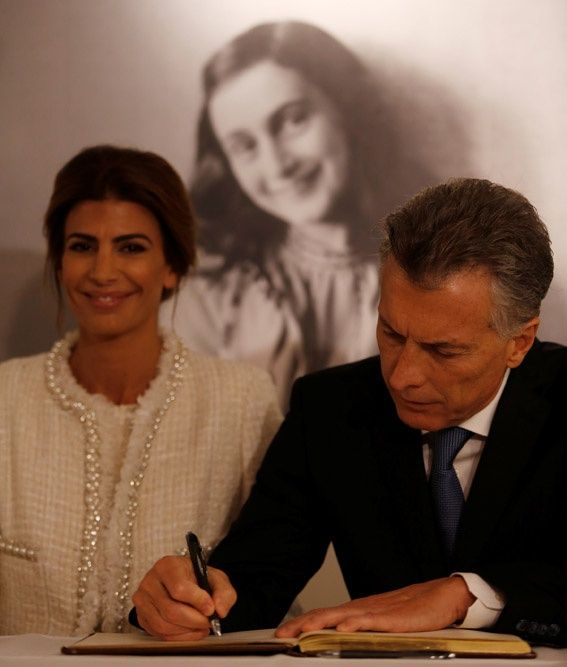 Argentina's President Mauricio Macri and his wife Juliana Awada sign the guest book as they sit in front of an image of Anne Frank during a visit to the Anne Frank House in Amsterdam, Netherlands - Argentina's President Mauricio Macri and his wife Juliana Awada sign the guest book as they sit in front of an image of Anne Frank during a visit to the Anne Frank House in Amsterdam, Netherlands, March 27, 2017. REUTERS/Cris Toala Olivares